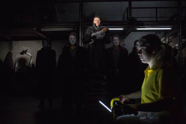 Frances Barber (as Caesar) in center amidst seat of Caesar-masked comrades, Carrie Rocks as Soothsayer peddling in foreground. (Image via Donmar original production.)