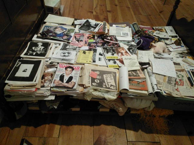 A child's mattress frame piled high with playbills and production ephemera -- piled high above and beneath. Image by Martha Wade Steketee.