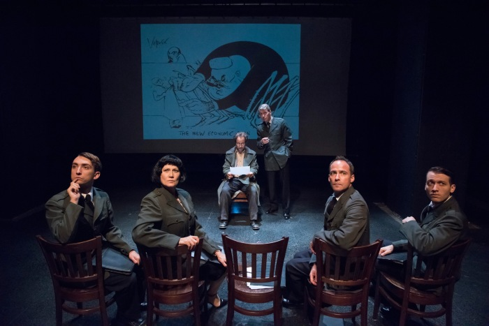[L-R upstage] Alex Draper, Jonathan Tindell + assembled interrogators. Image by Stan Barouh with Gerald Scarfe projected illustration.